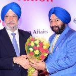 Sr. Vikram Sahney felicitating Sr. Hardeep Puri ji with a bouquet.